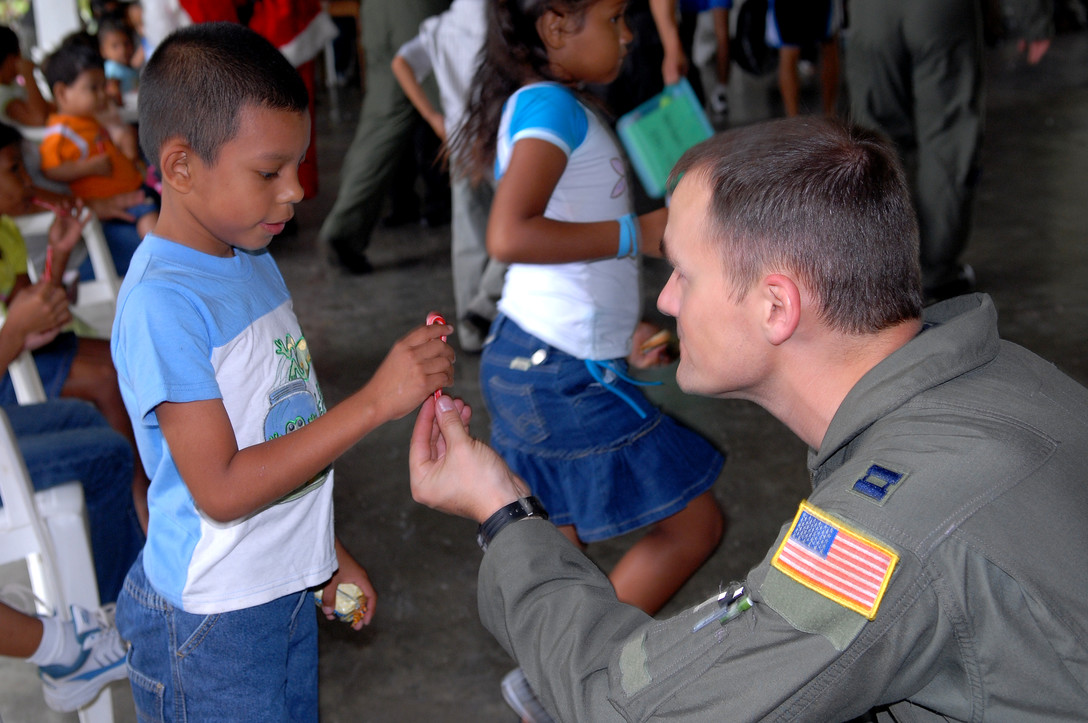 Capt. Patrick Dube, an aircraft commander with the 9th Special Operations Squadron, hands a Honduran orphan a candycane at Aldea Infantil S.O.S Orphanage in La Ceiba, Honduras during Operation Christmas Wish Dec. 13. Captain Dube was part of a 16-person team that helped deliver more than 875 Christmas packages to five different Honduran orphanages. (U.S. Air Force photo/Senior Airman Ali Flisek)